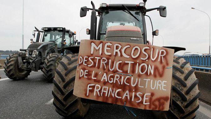 """Trator bloqueia rodovia. Em uma placa, lê-se, em francês """"Mercosur Destruction de L'Agriculture Française"""""""