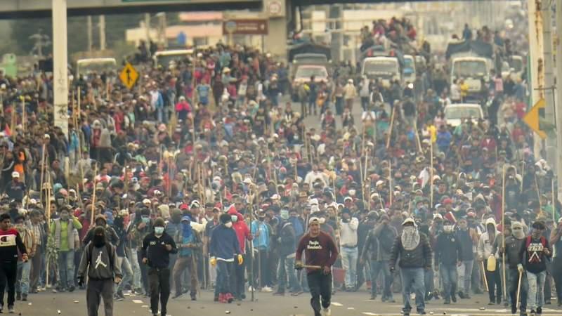 Manifestação massiva no equador, com manifestantes avançando com bastões