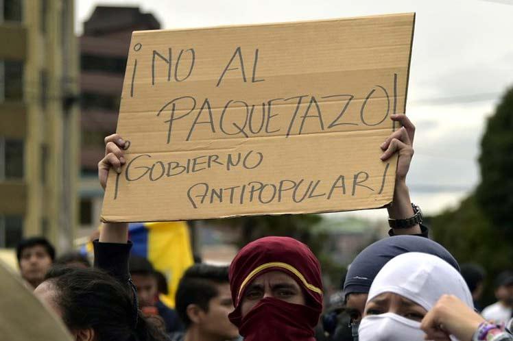 """Em manifestação no Equador, manifestante segura cartaz onde se lê """"No al paquetazo! Gobierno Antipopular!"""""""