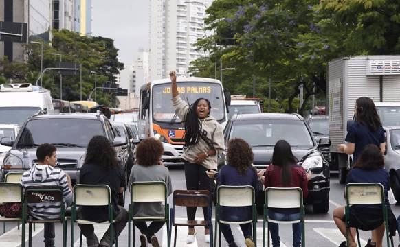 Estudantes secundaristas sentados em cadeiras, mas no meio da rua, segurando o trânsito. Uma menina negra de pé de costas para os carros e de frente para os estudantes, com o braço direito levantado.