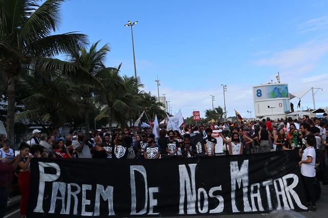 """Manifestação com uma grande faixa dizendo """"Parem de nos matar"""""""