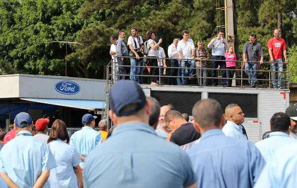 Trabalhadores da Ford de costas, de macacão azul, em frente a um carro de som no qual fala ao microfone membros do sindicato. Logotipo da Ford ao fundo.
