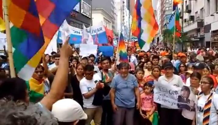 Foto de manifestantes na Bolívia, reunidos com faixas e cartazes, e a Whipala, a bandeira dos povos da América