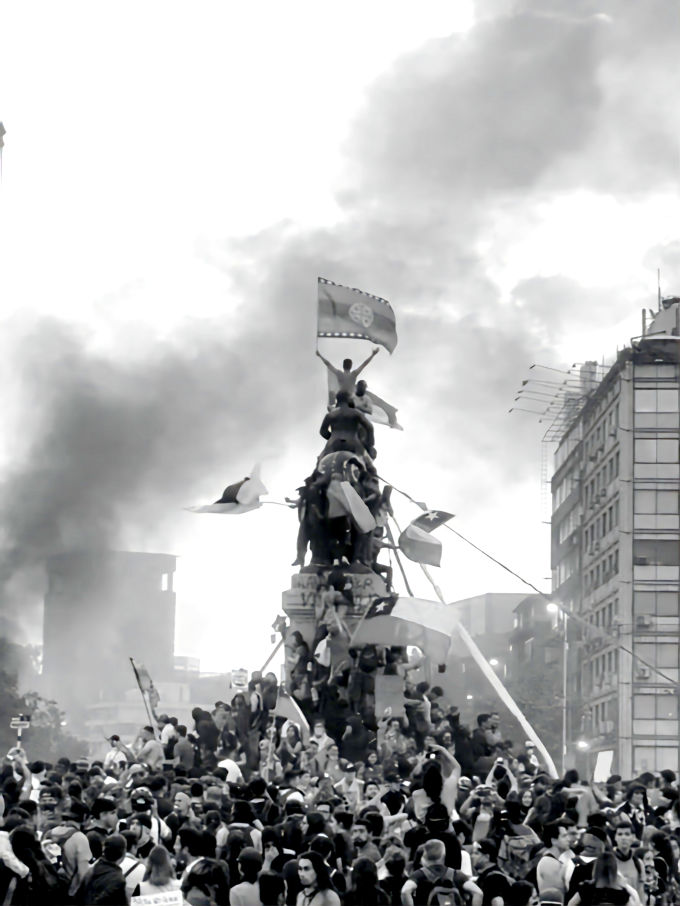 Foto em que manifestantes sobem em um monumento na capital chilena. A bandeira mapuche é hasteada.