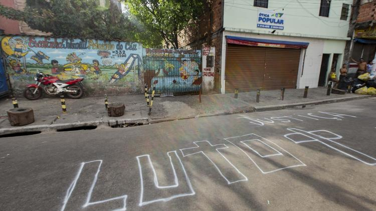 """Fotografia de uma rua de Paraisópolis, onde no asfalto está escrito com giz: """"Luto"""""""