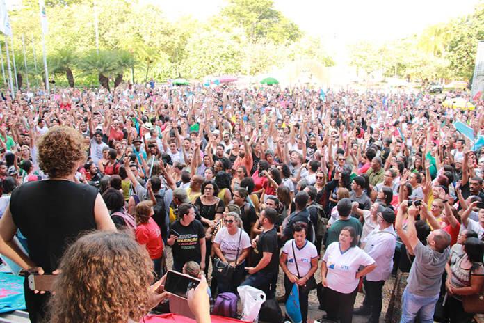 Fotografia de assembleia de professores em Minas Gerais. Milhares de professores com os braços levantados em uma votação