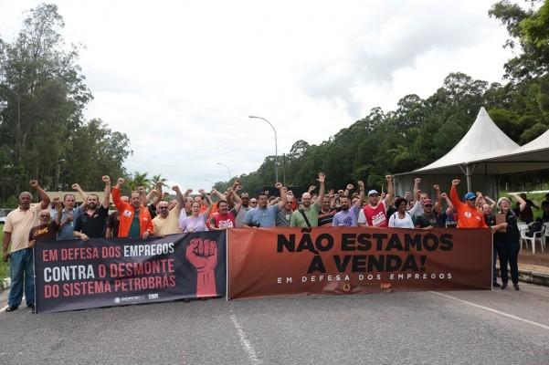 """Foto dos petroleiros na greve de 2020, com os punhos levantados e com uma faixa onde se lê """"em defesa dos empregos - contra o desmonte do sistema petrobrás"""" e """"não estamos à venda - em defesa dos empregos"""""""