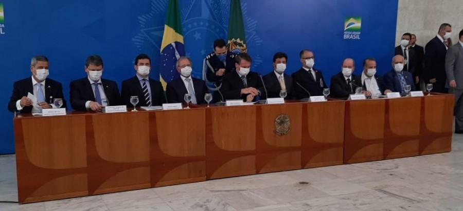 Bolsonaro e ministros sentados dando entrevistas. Todos usam máscaras.