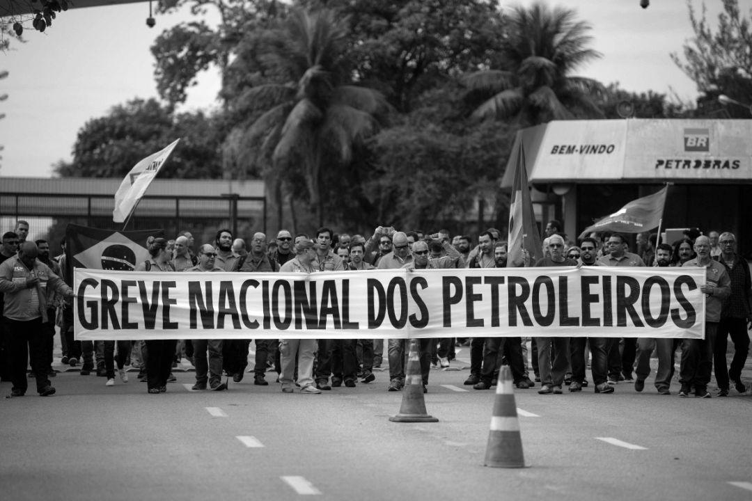 """Fotografia em preto e banco de petroleiros em frente à Petrobras com uma faixa onde se lê """"Greve Nacional de Petroleiros"""""""