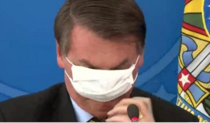 Imagem de Bolsonaro em coletiva de imprensa, olhando para baixo, enquanto ajusta desajeitadamente máscara cirúrgica no rosto