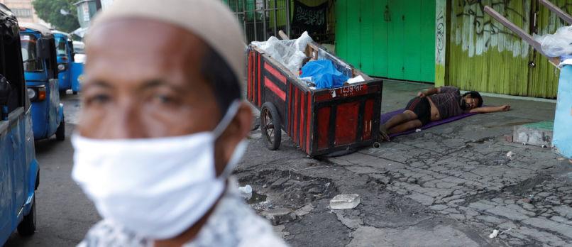 Um homem usando uma máscara. Ao fundo, um carrinho de materiais recicláveis e um trabalhador em situação de rua dormindo ao seu lado, no chão