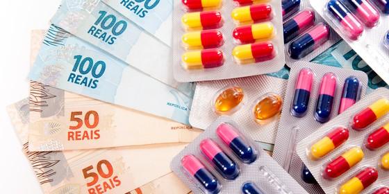 Foto de tarjetas de remédios em cápsula junto a notas de dinheiro