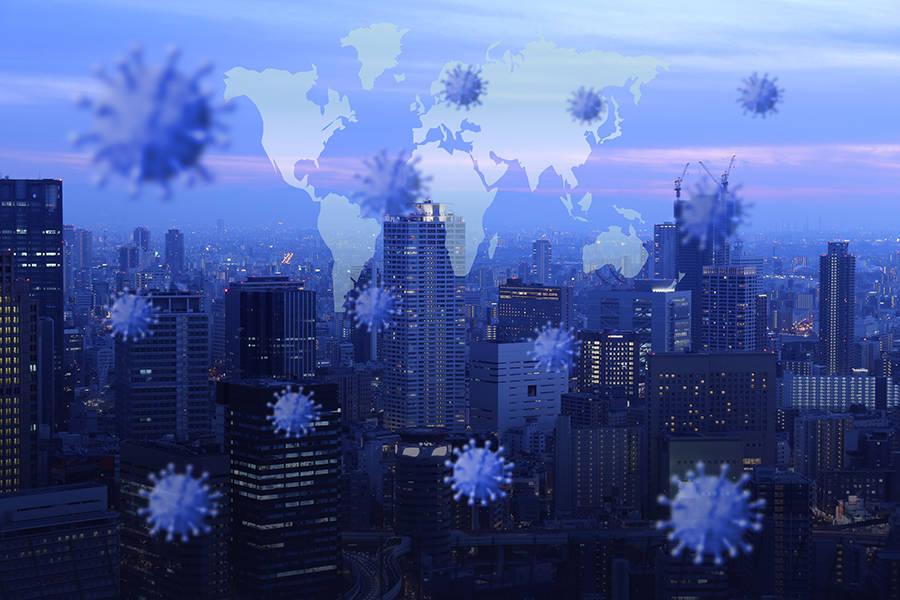 Em primeiro plano, a figura de diversos coronavirus, em segundo plano o mapa-mundi, ao fundo a fotografia de uma grande cidade, com muitos prédios