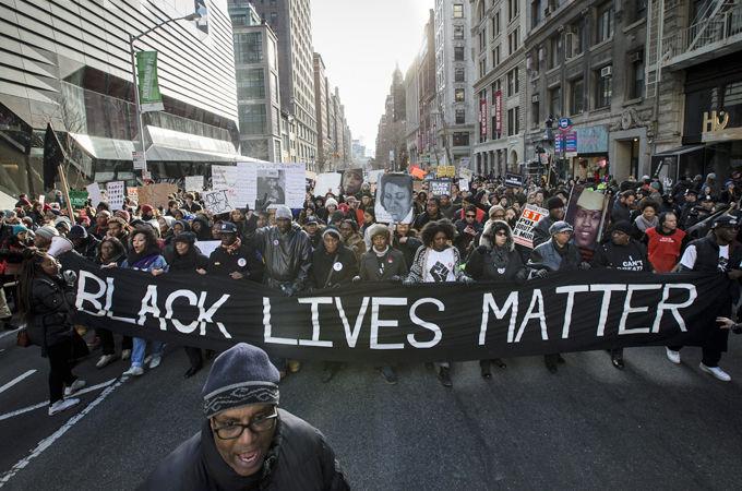 """Manifestação nos Estados Unidos contra o racismo. Um homem negro em primeiro plano e, após ele, uma passeata com uma grande faixa na frente, onde está escrito """"Black lives matter"""""""