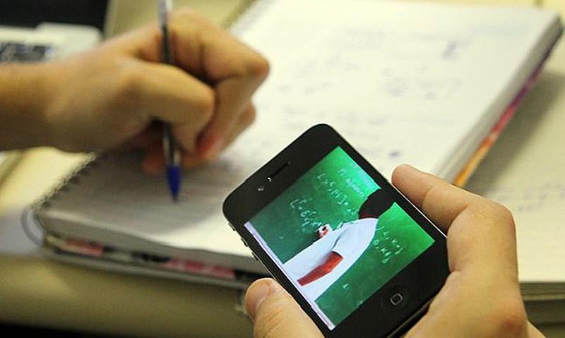 Uma pessoa segura um celular enquanto, com a outra mão, escreve em um caderno. No celular, um professor escreve em um quadro verde.