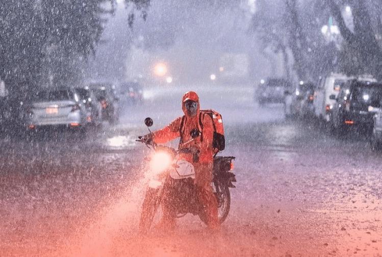 Fotografia de entregador de aplicativo em sua moto, sob chuva pesada