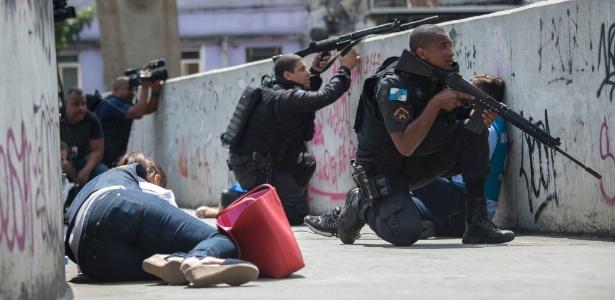Uma pessoa alvejada ou deitada ao chão, no meio da rua, e uma sacola vermelha e policiais de metralhadoras empunhadas se protegem agachados a um muro.