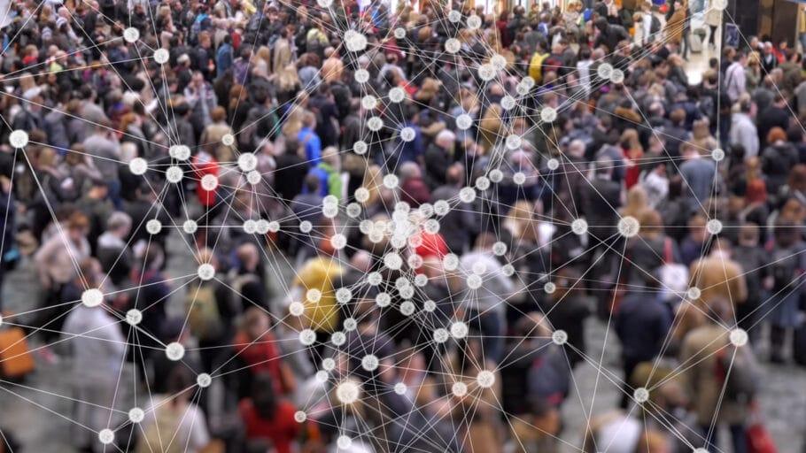 Fotografia de aglomeração de pessoas em segundo plano. Em primeiro plano, um grafo com várias conexões, ilustrando a falta de distanciamento social entre elas.