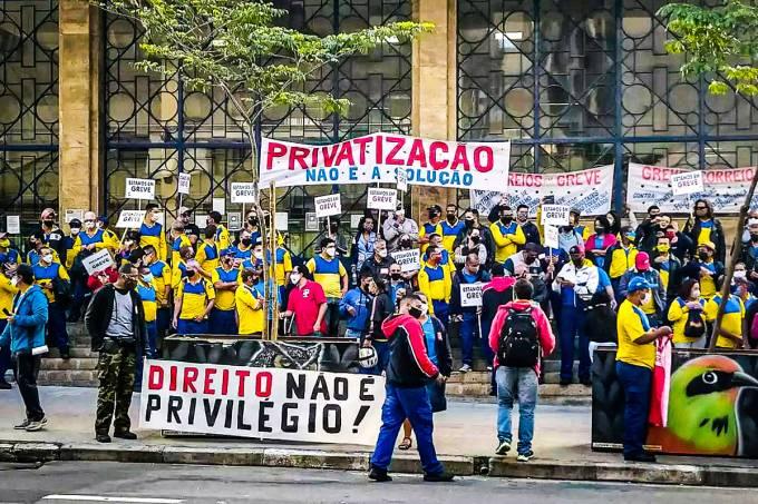"""Fotografia dos trabalhadores dos Correios em greve. Em duas faixas lê-se """"Privatização não é a solução"""" e """"Direito não é privilégio""""."""