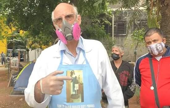 Fotografia do Padre Júlio Lancelotti de máscara, luvar e apoiadores ou moradores em situação de rua ao fundo