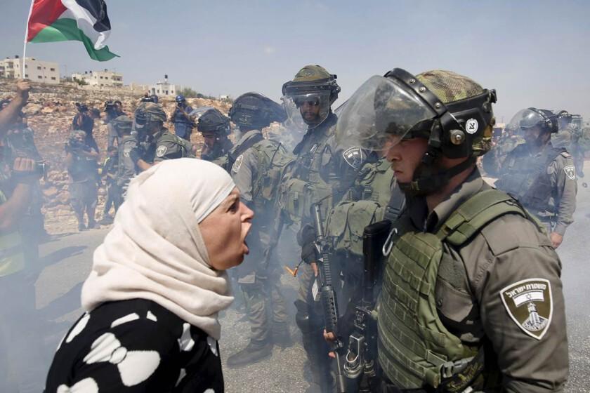 Fotografia de mulher palestina gritando contra soldado do exército de Israel que reprime uma repressão. Gás e a bandeira palestina tremula ao fundo.