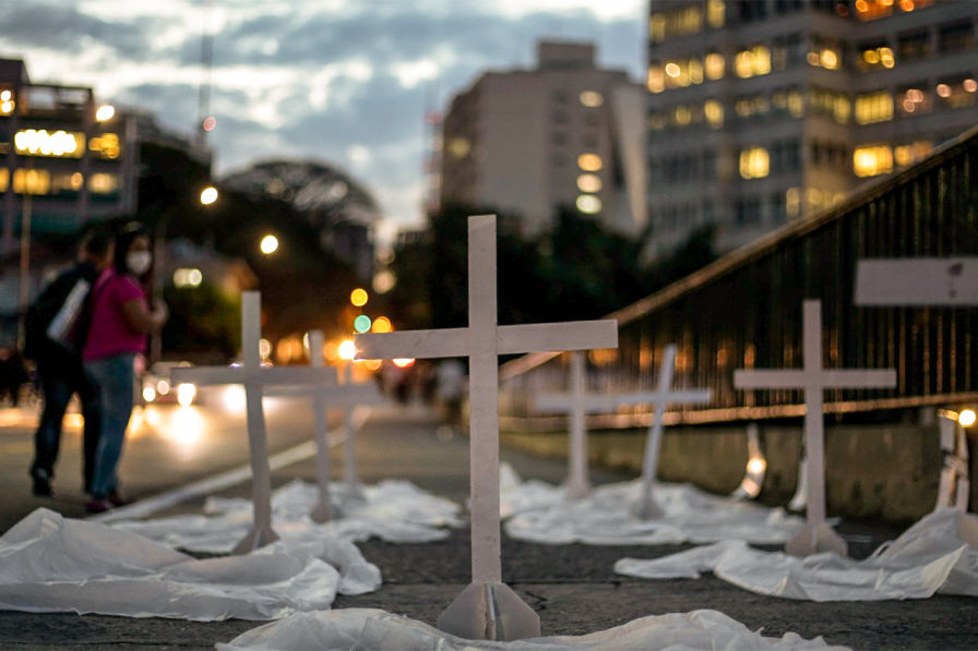 A imagem mostra cruzes brancas colocadas sobre uma calçada ao anoitecer, com luzes dos prédios e farois dos carros ao fundo. Depois das cruzes, uma mulher com uma máscara olha para trás, para as cruzes.
