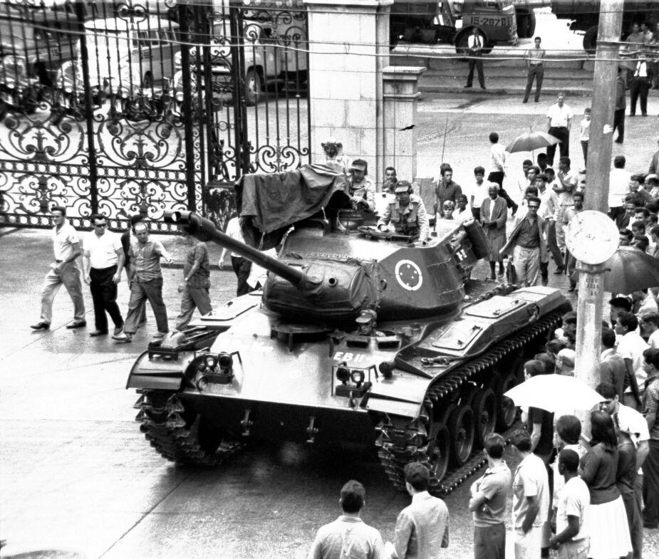Imagem de tanque de guerra, com soldados em cima e civis apoiadores à volta