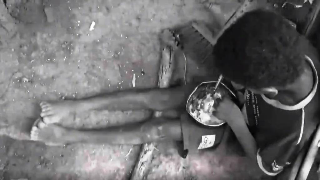 Menino descalço e sendado no chão sujoé fotografado de cima para baixo, comendo uma marmita.